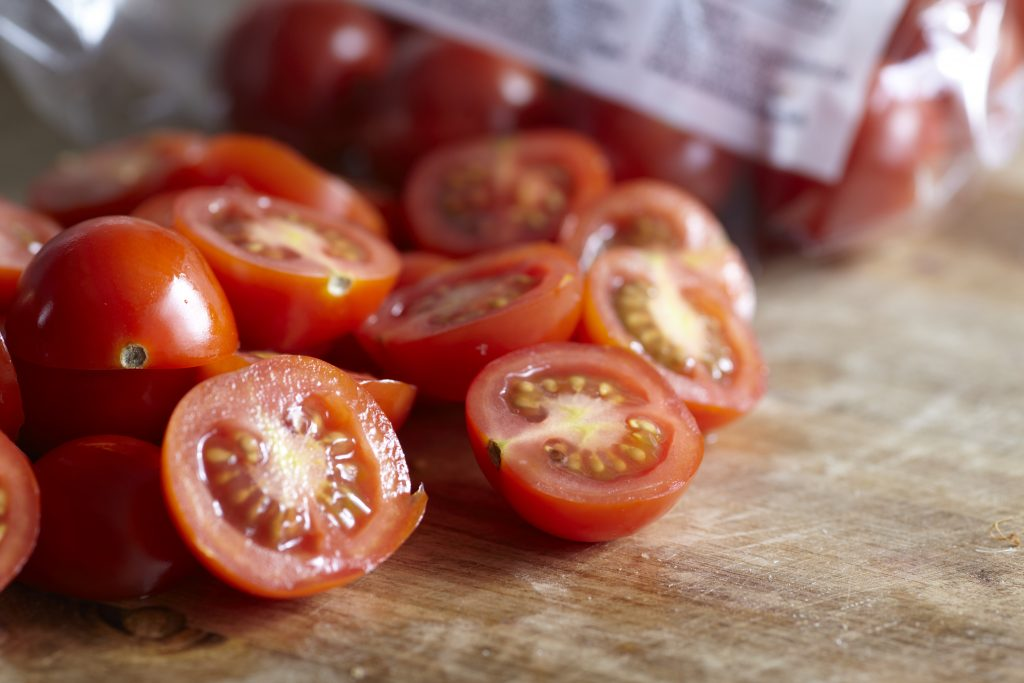 Freshly sliced cherry tomatoes on a wooden chopping board.