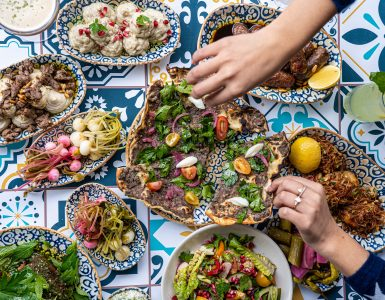 Hands reach for a Middle Eastern feast