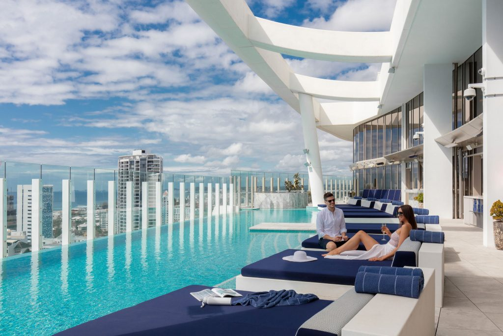 Couple lounging by rooftop pool